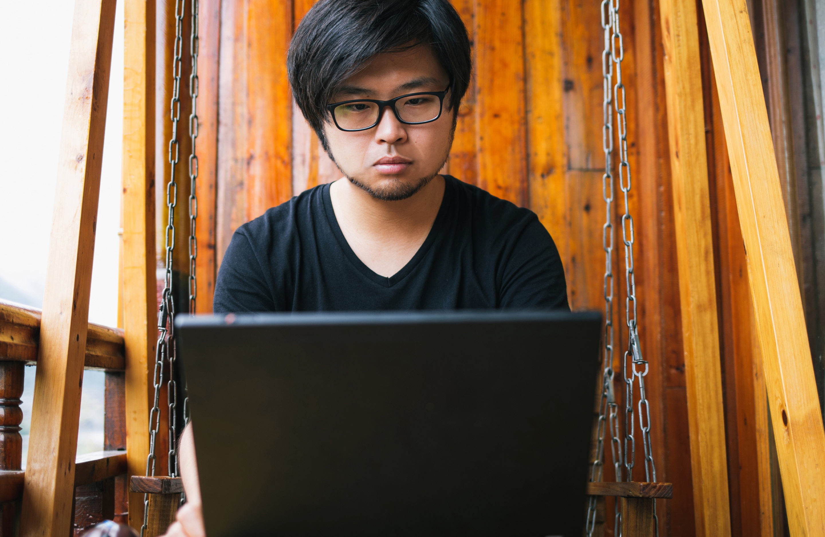 Asian man looking at laptop